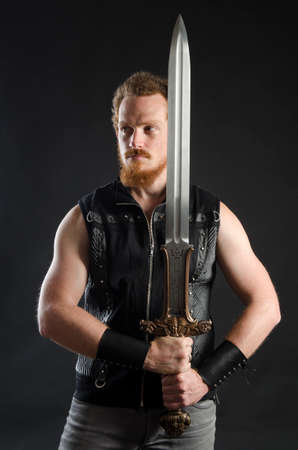 Cosplay portrait of a redhead bearded man holding a two-handed sword. Background is black. Stok Fotoğraf - 147749832