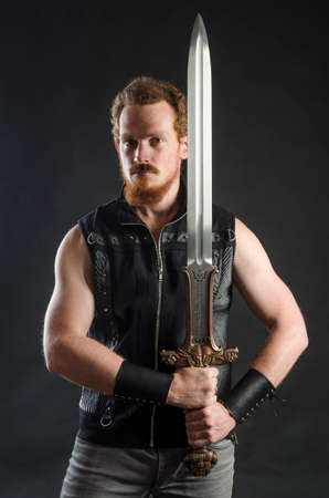 Cosplay portrait of a redhead bearded man holding a two-handed sword. Background is black. Stok Fotoğraf - 147749833