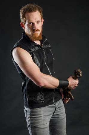 Cosplay portrait of a redhead bearded man holding a two-handed sword. Background is black. Stok Fotoğraf