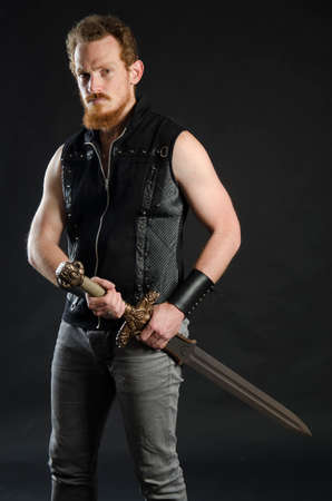 Cosplay portrait of a redhead bearded man holding a two-handed sword. Background is black. Stok Fotoğraf - 147749836