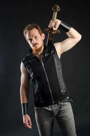 Cosplay portrait of a redhead bearded man holding a two-handed sword. Background is black. Stok Fotoğraf - 147749838