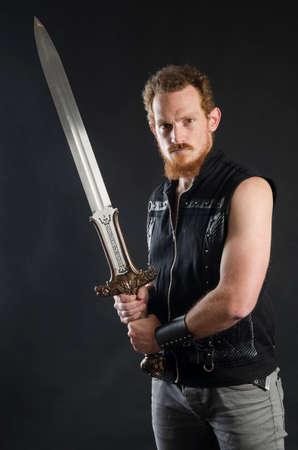 Cosplay portrait of a redhead bearded man holding a two-handed sword. Background is black. Stok Fotoğraf - 147749839