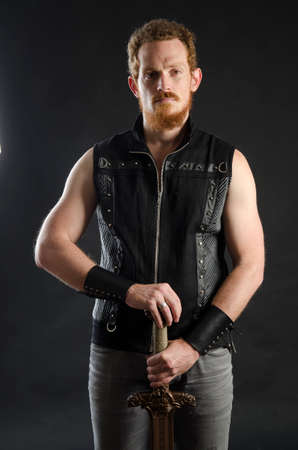 Cosplay portrait of a redhead bearded man holding a two-handed sword. Background is black. Stok Fotoğraf - 147749841