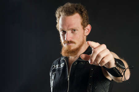 Cosplay portrait of a redhead bearded man holding a two-handed sword. Background is black. Stok Fotoğraf - 147749843