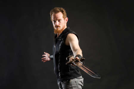 Cosplay portrait of a redhead bearded man holding a two-handed sword. Background is black. Stok Fotoğraf - 147749844