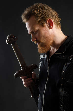 Cosplay portrait of a redhead bearded man holding a two-handed sword. Background is black. Stok Fotoğraf - 147749847