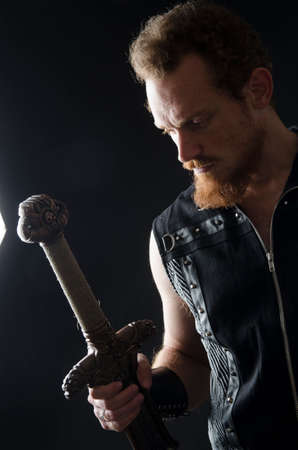 Cosplay portrait of a redhead bearded man holding a two-handed sword. Background is black. Stok Fotoğraf - 147749852