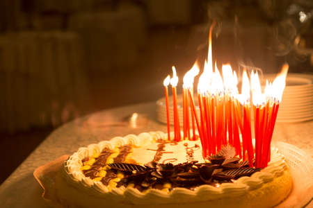 Detail of a birthday cake candles burning in a dark environment