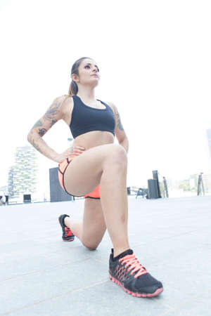 Street portrait of a beautiful fit girl performing sport training outdoors.