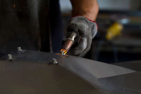 Close up on a welding machine in action, handheld by a worker wearing protective gloves.