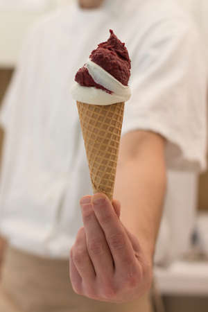 Detail of an ice cream man serving ice cream towards the camera.