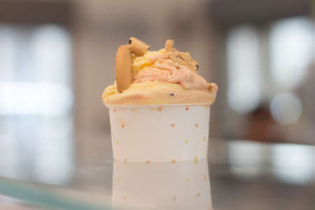 Close-up on a cup with ice cream resting on a table top. Stok Fotoğraf