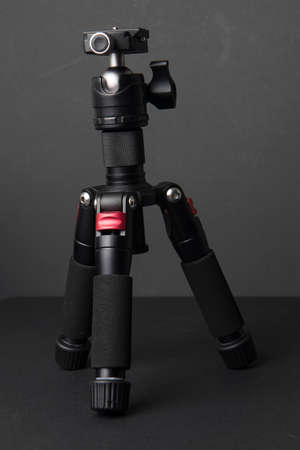 Close up on a photographic tripod resting on a neutral background, nobody is visible. Stock fotó