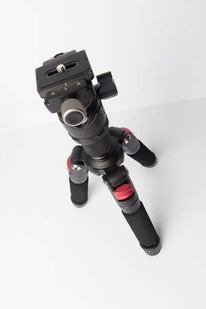 Close up on a photographic tripod resting on a neutral background, nobody is visible.