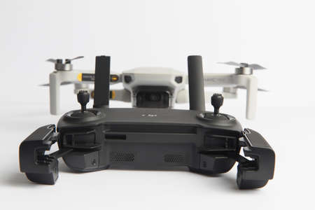 Milan, Italy - July 25, 2020: close up on a DJI Mavic Mini drone resting on a white background, no people are visible.