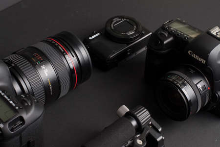 Milan, Italy - August 29, 2020: close up on Canon photographic equipment resting on a black background.