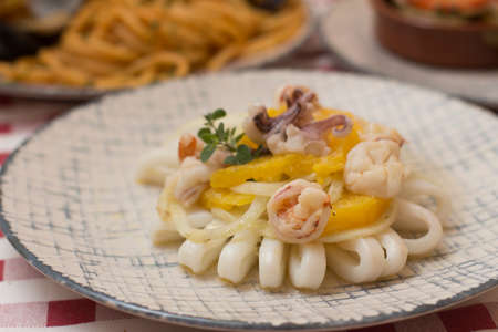 Spanish style squid calamari salad served on a restaurant table top. No people are visible. Reklamní fotografie