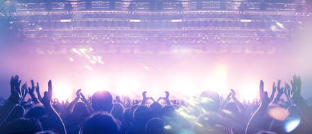Large assembly of people in front of a large stage lit in the dark.