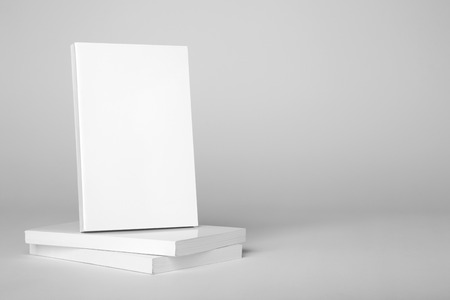 paperback: Real white paperback book over a stack of books on a gray background Stock Photo