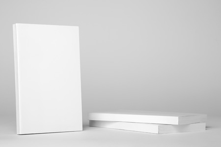 paperback book: Real white paperback book next to a stack of books on a gray background