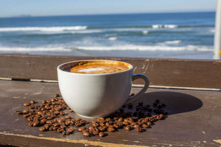delicious coffee latte in cup surrounded by coffee beans on beach bar terrace terrace in a relaxing atmosphere on vacation