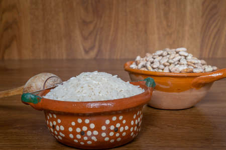 Mexican style clay containers with rice grains and beans on wooden boards with wooden handmade spoon Stock Photo
