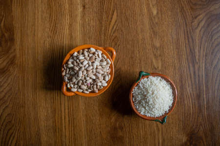 top view of Mexican style clay containers with rice grains and beans on wooden boards Stock Photo