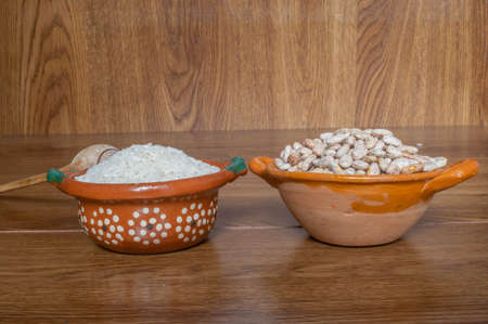 Mexican style clay containers with rice grains and beans on wooden boards