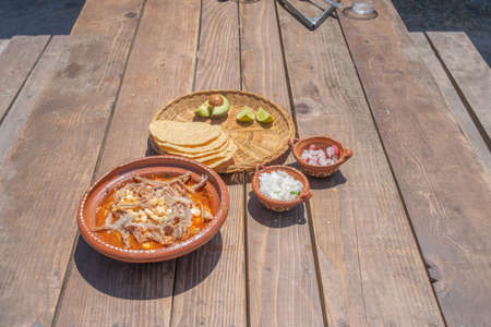 Mexican food dish. pozole with toasts, avocado and onion Фото со стока