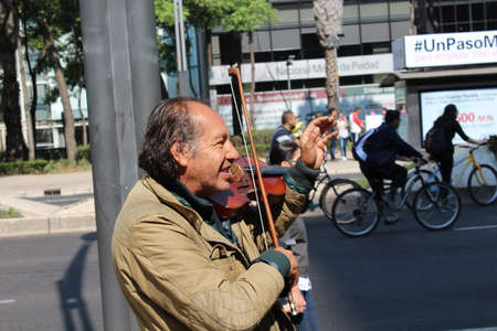 MEXICO CITY, MEXICO - February / 04 / 2017 POOR MAN PLAYING THE VIOLIN IN THE STREET
