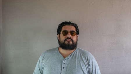 fat latin man with beard wearing aviator glasses