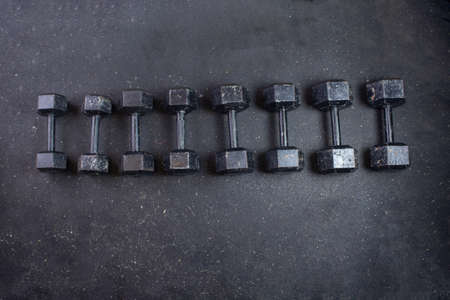 dumbbells of different sizes and weights in gym. fitness background