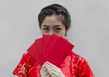 pretty chinese young woman holding red bags for happy chinese new year photo