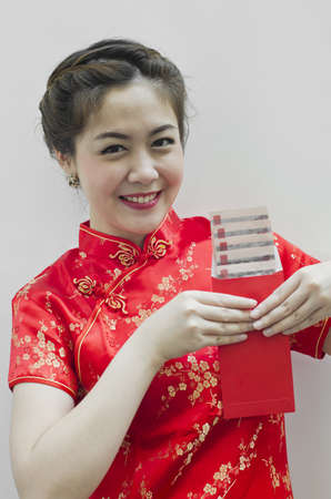red packet: pretty chinese young woman holding red bag for happy chinese new year