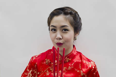 chinese young woman with tradition clothing holding joss sticks(incense) photo