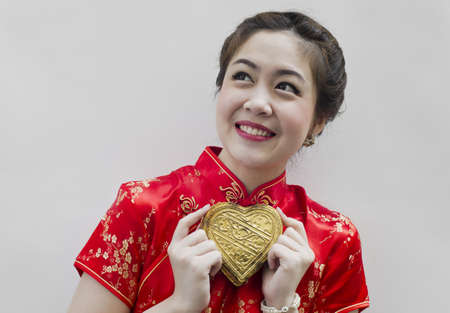 Beautiful asian woman wear cheongsam and holding golden heart photo