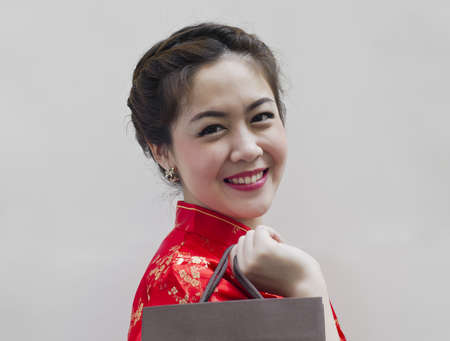 pretty woman in red Traditional Chinese Cheongsam with shopping bag photo