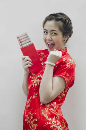 smiling beautiful chinese woman holding the red money envelope photo
