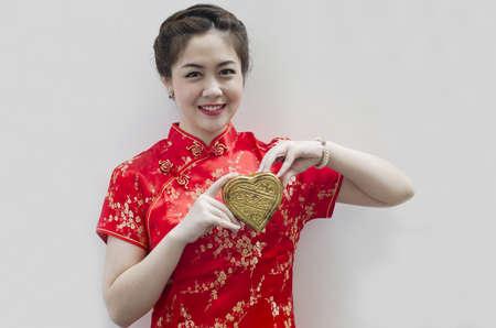 Beautiful asian woman wear cheongsam and holding golden heart photo