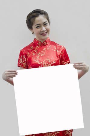 Oriental girl wishing you a happy chinese new year, with copy space. Stock Photo - 12004842