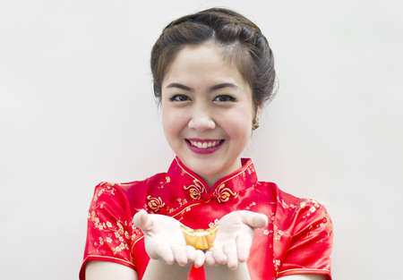 Beautiful asian woman wear cheongsam and holding chinese gold ingot photo
