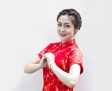 cheongsam: happy Chinese new year. beautiful young Asian woman with gesture of congratulation
