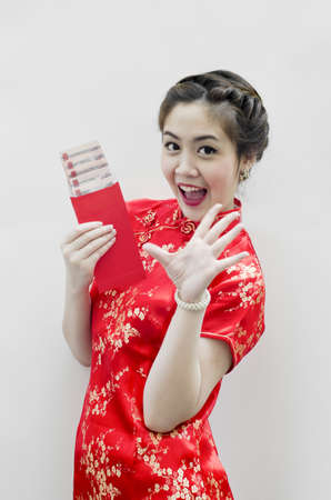 pretty chinese young woman holding red bag for happy chinese new year photo