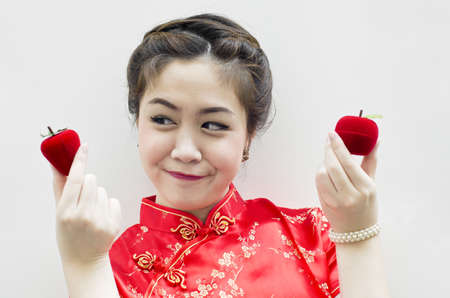 smiling beautiful chinese woman holding a strawberry and an apple photo
