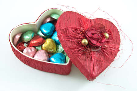 opening Red heart box with colorful chocolate background,isolated photo