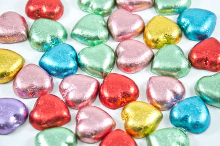 colorful chocolate hearts candies on white background,isolated photo