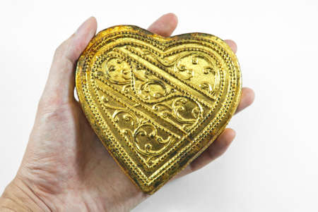 hand holding playing card: Hands holding golden heart, white background