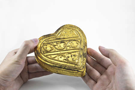 Hands holding golden heart, white background photo