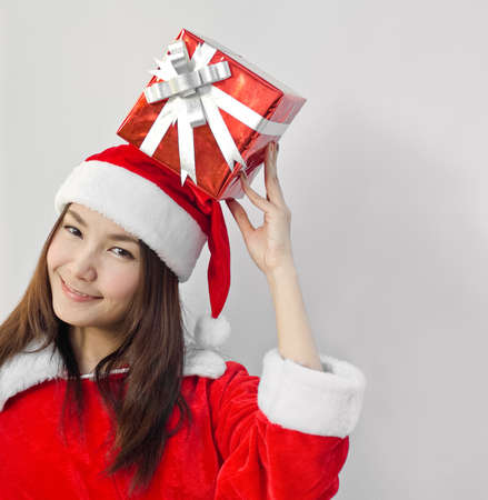 Portrait of young beautiful woman in santa claus hat with red christmas gift box with grey ribbons. photo