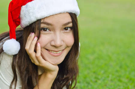 christmas ground: Beautiful young santa clause woman in christmas clothes smiling on the ground Stock Photo